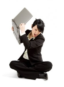 Woman frustrated, throwing her laptop